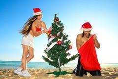Ayudante y Santa de Santa en la playa tropical Imagen de archivo libre de regalías