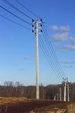 Ayudas con los alambres de la línea eléctrica contra el cielo azul Imágenes de archivo libres de regalías