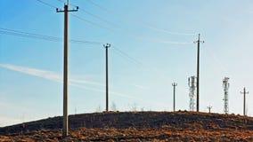 Ayudas de la línea eléctrica en la colina en la puesta del sol Fotografía de archivo libre de regalías