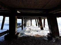 Ayudas debajo del embarcadero en Southwold en un día de invierno frío Foto de archivo libre de regalías