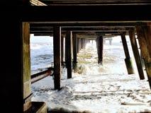 Ayudas debajo del embarcadero en Southwold en un día de invierno frío Imagen de archivo libre de regalías