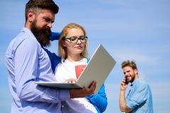 Ayudas del aire fresco para restaurar mente Día soleado al aire libre del trabajo del ordenador portátil de los colegas, fondo de Imagenes de archivo