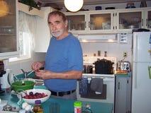 Ayudas del hombre con el enlatado de la fruta del ciruelo Foto de archivo