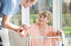 Ayudas del hombre para levantarse a una más vieja mujer Foto de archivo libre de regalías
