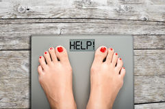 Ayude a perder kilogramos con los pies de la mujer que caminan en una escala del peso imagen de archivo libre de regalías
