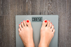 Ayude a perder kilogramos con los pies de la mujer que caminan en una escala del peso fotos de archivo