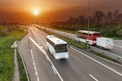 Ayunan los autobuses del viaje en la falta de definición de movimiento en la carretera en la puesta del sol Imagen de archivo libre de regalías
