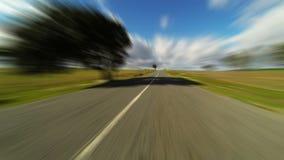 Ayune conduciendo el coche en el camino en campos verdes