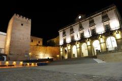 Ayuntamiento y terraplenes medievales iluminados en la noche, Caceres, Extremadura, España Foto de archivo libre de regalías
