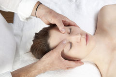 Ayurveda face massage for soothing headache. Meridian facial stress relief with acupressure practice Stock Photos