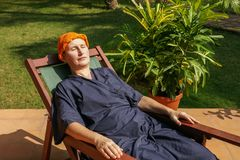 Ayurveda-treatment. Woman has a rest after an ayurveda-application, on her head a herbal pack stock image