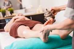 Ayurvedic foot therapy massage procedure with oil. In spa royalty free stock photo
