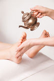 Ayurvedic foot therapy massage procedure with oil. In spa stock photography