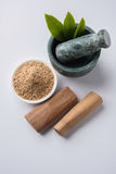 Ayurvedic sandalwood powder, oil and paste. Chandan or sandalwood powder with traditional mortar, sandalwood sticks, perfume or oil and green leaves. selective Royalty Free Stock Photo