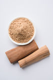 Ayurvedic sandalwood powder, oil and paste. Chandan or sandalwood powder with traditional mortar, sandalwood sticks, perfume or oil and green leaves. selective Royalty Free Stock Image