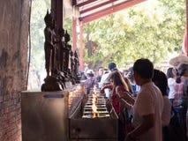 AYUTHAYA THAILAND MAY 03,2015: Folket fyller någon olja för olje- lampa Royaltyfria Bilder