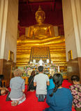 AYUTHAYA, THAILAND - 22 NOV 2013: Worshippers pray near the stat Royalty Free Stock Photos