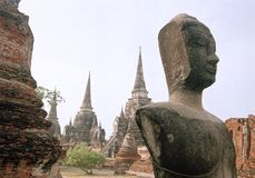 Ayuthaya weathered buddha temple thailand. Half headed buddha statue contemplates the temple ruins of Ayuthaya the ruined capital of thailand stock photos