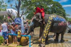 AYUTTHAYA, TAILANDIA - 14 DE ABRIL: Los jaraneros gozan del agua que salpica con los elefantes durante el festival de Songkran el Imagen de archivo