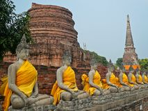 Ayutthaya, Thailand. Ancient temple in Ayutthaya, Thailand with the sculptures of Buddha sitting in a row and yellow cloth on them stock photography
