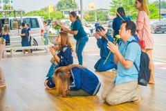 AYUTTHAYA THAILAND, FEBRUARI, 08, 2018: Utomhus- sikt av oidentifierat folk som ber på deras knä inom av en tempel Royaltyfri Fotografi