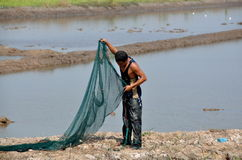 Ayutthaya, Thailand: Fisherman with Net. A fisherman holds a large net that he is preparing to cast into the water at a fisheries farm in the Ayutthaya, Thailand royalty free stock photo