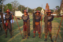 AYUTTHAYA,THAILAND - MARCH 17,2013 : Ancient Thailand warriors in historical armor with shields and spears on background of stupas. Wai Kru Ceremony is a royalty free stock photo