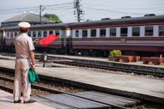 Ayutthaya, 01 Thailand-November 2017: Het treinpersoneel maakt tot een signaal met rode vlag aan mensen dat de trein aankomt Stock Afbeeldingen