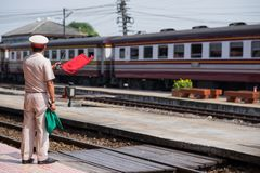 Ayutthaya,Thailand-November 01 2017 :Train staff Make a signal with red flag to people that train arrives. To the station Stock Images