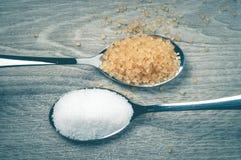 Azúcar blanco y azúcar marrón, y cuchara Fotografía de archivo