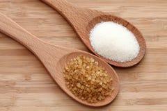 Azúcar blanco y marrón en cucharas de madera Foto de archivo libre de regalías