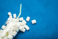 Azúcar cristalino en zumo o soda de fruta, en un fondo azul imagen de archivo
