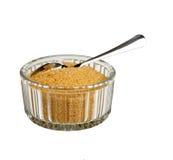 Azúcar de Brown en tazón de fuente con la cuchara, aislada Imagen de archivo