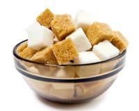 Azúcar de caña refinado y marrón del blanco. Aún-vida en un fondo blanco Fotos de archivo libres de regalías