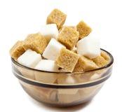 Azúcar de caña refinado y marrón del blanco en un cuenco. Aún-vida en un fondo blanco Foto de archivo