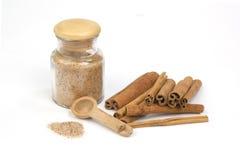 Azúcar de Cinamon con los palillos del cinamon aislados en blanco Foto de archivo libre de regalías