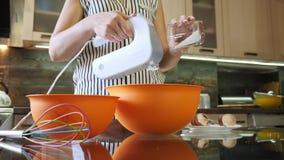Azúcar de colada de la mano de la mujer en el cuenco Ingredientes de mezcla para cocinar la torta metrajes