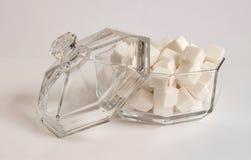 Azúcar de terrón Cuenco de azúcar de cristal con la tapa en el fondo blanco Fotos de archivo libres de regalías