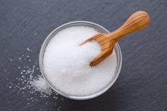 Azúcar del xilitol o del abedul en una cucharada y un bol de vidrio de madera en el fondo negro, foco selectivo Imagen de archivo libre de regalías