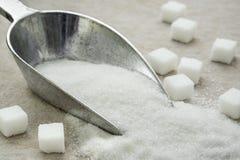 Azúcar en la cucharada del metal Foto de archivo libre de regalías