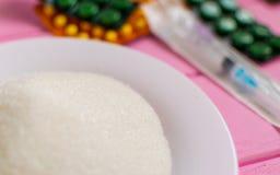 Azúcar en una placa, una jeringuilla y píldoras en un fondo rosado Fotos de archivo