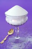 Azúcar granulado blanco puro en un vidrio de la vendimia en un Backg púrpura Fotografía de archivo libre de regalías