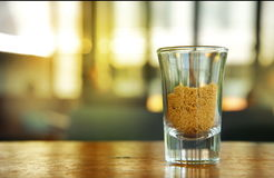 Azúcar marrón orgánico en vaso de medida en la tabla de madera con la naranja caliente Imagen de archivo