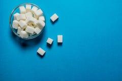 Azúcar refinado en la taza En la tabla azul fotos de archivo