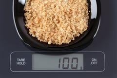 Azúcares de caña de Brown en escala de la cocina Fotos de archivo libres de regalías