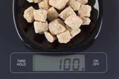 Azúcares de caña de Brown en escala de la cocina Foto de archivo