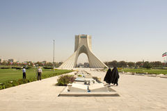 Azadi Tower. Image Azadi Tower in the Iranian capital Tehran, and two Iranian girls walking in front of the monument stock photos