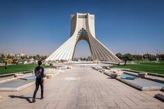 Azadi Tower in Tehran. Tehran, Iran - October 15, 2016: Man walks in front at Azadi Square with Azadi Tower in Tehran stock image