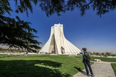 Azadi Tower in Tehran. Tehran, Iran - October 15, 2016: Western tourist in front of one of the most famous Tehran landmarks - Azadi Tower located at Azadi Square royalty free stock image