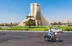 Azadi Tower in Tehran. Tehran, Iran - October 15, 2016: Man drives scooter in front of famous Teheran landmark Azadi Tower on Azadi Square stock photo